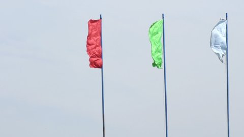 Multicolored festive flags evolve in the wind against a blue sky, background, festive, slow motion, copy space