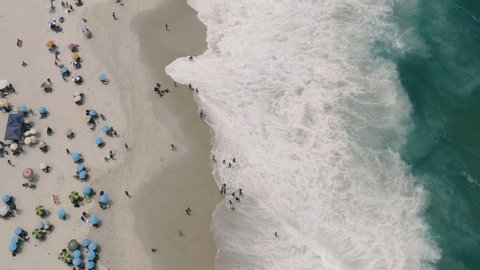 Drone: Top view the crowded golden beach of Rio de Janeiro while the waves of the sea reach the tourists. Brazil