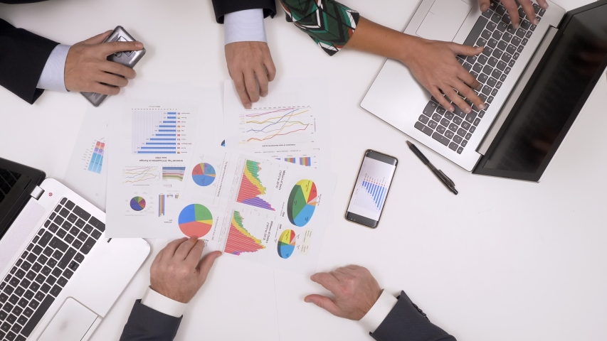 Top view of Business team checking financial charts and graphs #1030398104