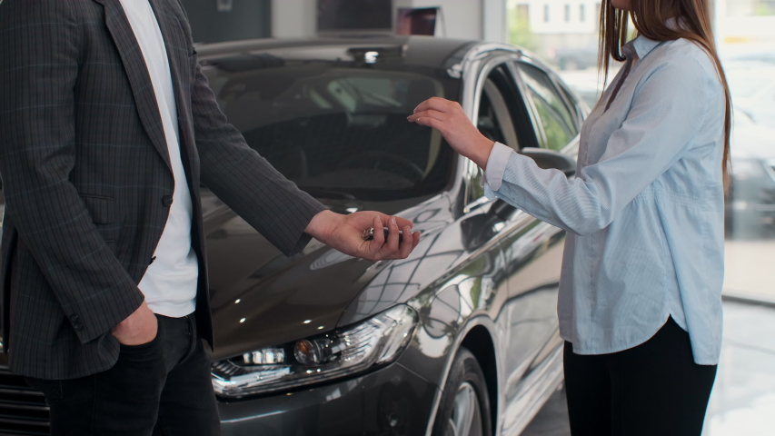 Famale hand gives a car keys to male hand in the car dealership close up. Unrecognized auto seller and a woman who bought a vehicle shake hands. | Shutterstock HD Video #1030426964