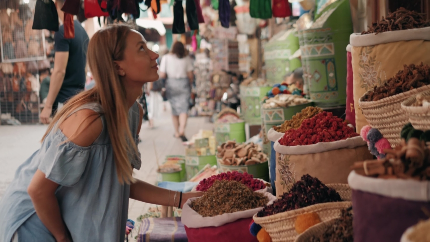 Woman walking on MAROCCAN MARRAKECH spices market. Woman walking on beautiful african arabian spices market and choose spices, travel tourist | Shutterstock HD Video #1030470494