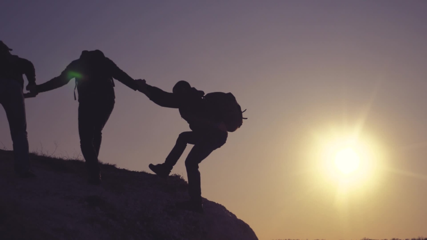 Teamwork help business lifestyle travel silhouette concept. group of tourists lends a helping hand climb the cliffs mountains. people climbers climb to the top overcoming hardships the path to victory | Shutterstock HD Video #1030475594