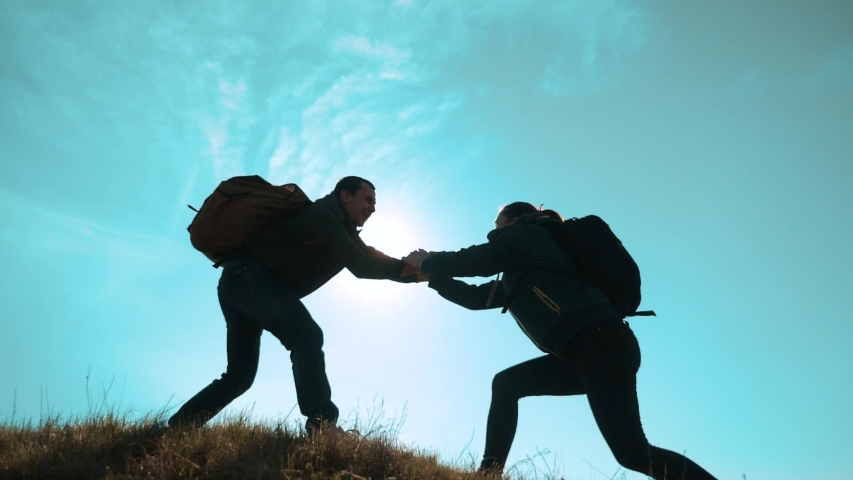 Happy family teamwork help business travel concept. two hikers man and woman tourists climbers climb to the top of the mountain. extends a helping hand overcoming hardships teamwork the path to | Shutterstock HD Video #1030475654