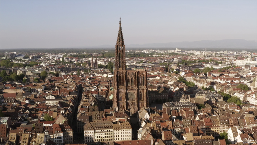 Strasbourg and its cathedral Notre Dame de Strasbourg in an aerial shot filmed in 4K on a sunny day. The drone is flying around the religious building. | Shutterstock HD Video #1030484084