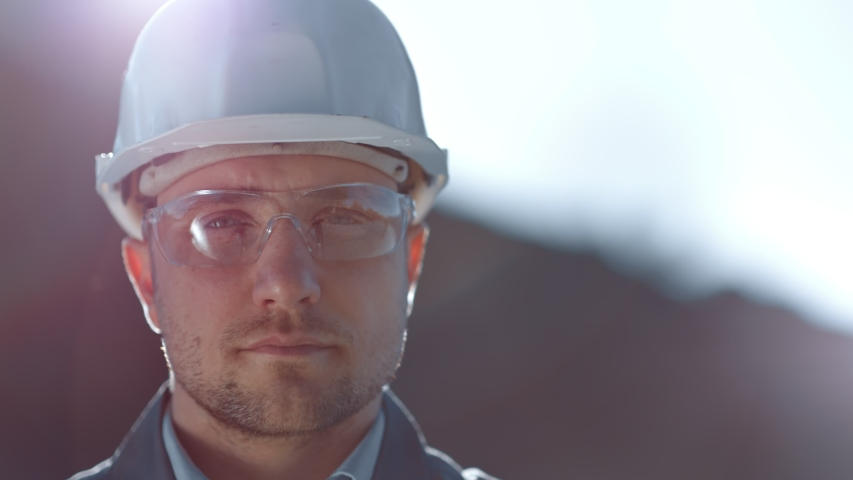 Close-up portrait of male industrial worker wearing glasses and helmet looking at camera | Shutterstock HD Video #1030490204