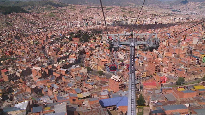 Wide low-angle back shot from a transiting cable car of an opposite moving cabin above La Paz city buildings, Bolivia | Shutterstock HD Video #1030499084