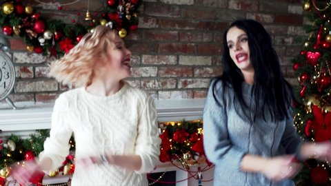 Slow motion of two women in warm desses and stockings dancing in Christmas decorations