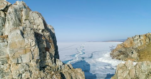 Tranquil Aerial View of Famous tourist destination. Winter Baikal Top view drone footage. Symbol of Lake Baikal Cape Burhan in winter time