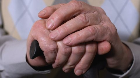 Aged male hands on walking stick close-up, social pension reforms, health care