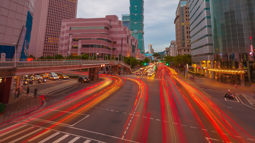 Time lapse of Taipei city skyline and downtown view before sunset overlooking Taipei 101 and Xinyi District busy crossroad with light trails in asia.
