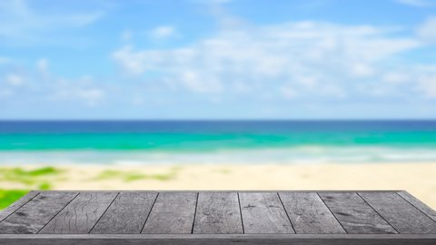 4K. UHD 2160p- Wooden table on outdoor beach sea in the summer blur sea background. For your product hear on top table.