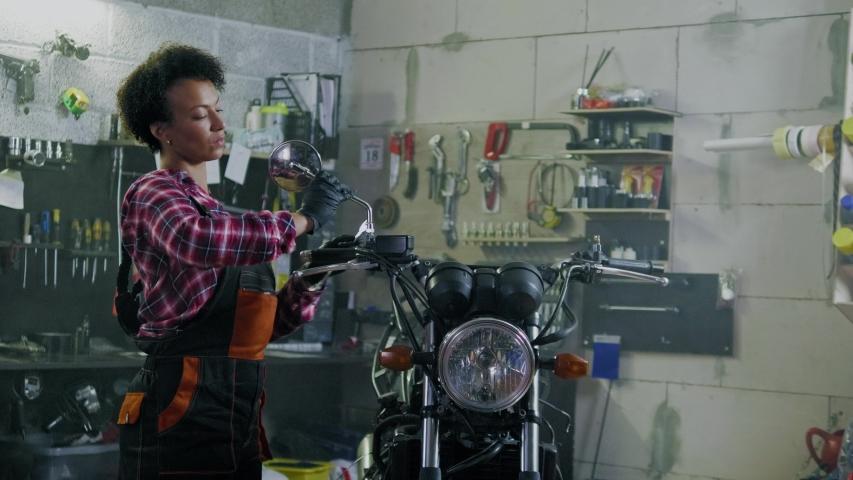 African american woman mechanic repairing a motorcycle in a workshop | Shutterstock HD Video #1030543364