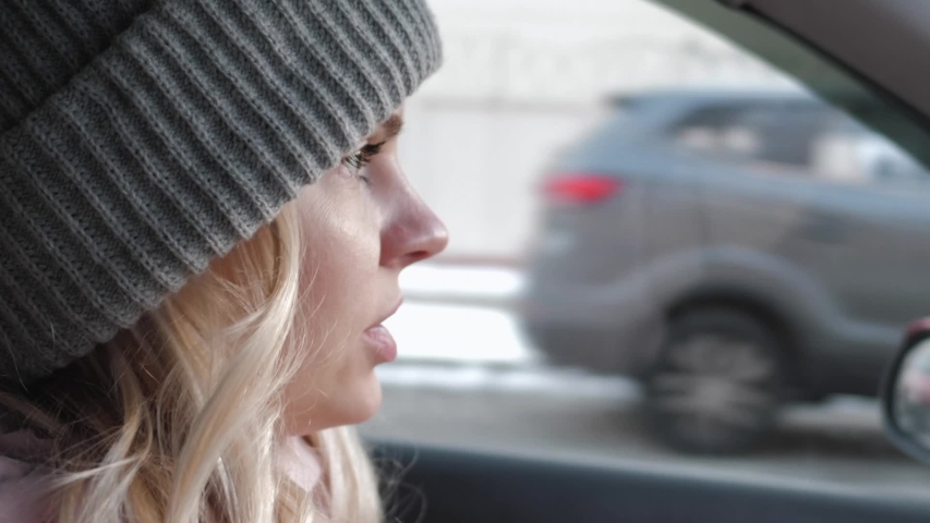 Young pretty blond woman with long curly hairstyle in grey sport knit hat, pink parka driving car through a city road traffic, rotating steering wheel, looking around, maneuver, give way to | Shutterstock HD Video #1030596014
