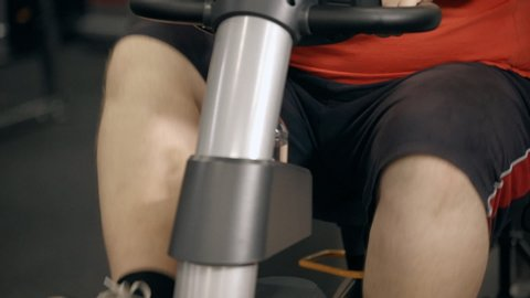 Close up and cropped body part view overweight knee of young man wearing in sportswear. He sitting on exercise bike inside modern city sport gym and start hard and long training after work day