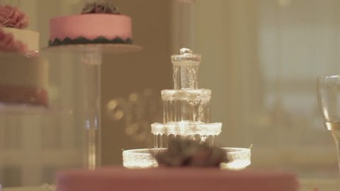 "Close up on decorative glass crystal flowing table fountain in romantic wedding setting, pulling focus back to focus on wedding cake with ""Mr & Mrs"" wording topper."