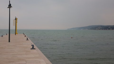 Steady shot of tiny pier and peaceful sea waters of Rodi Garganico marina, Italy