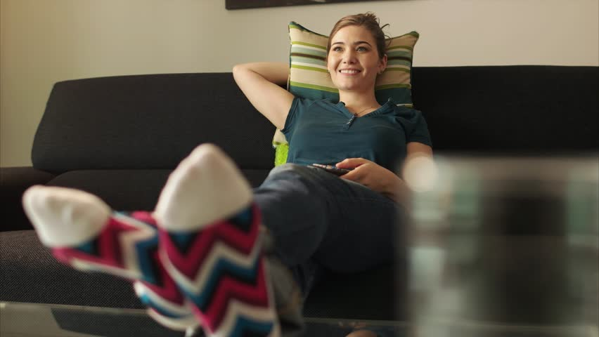 Young caucasian woman laying on sofa with colorful socks. She puts her feet on table and sits back. The girl watches TV and holds remote control