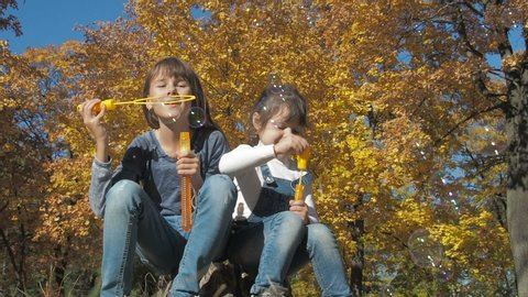 Children blowing bubbles outside. Girls blowing bubble in autumn park.
