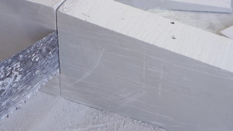 beauty slow motion in construction and repair - male builder sawing gypsum tongue-and-groove blocks
