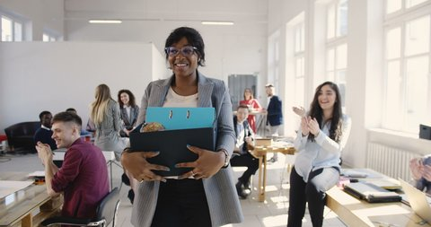 Beautiful young black female manager carrying office box, hired for a new job, multiethnic colleagues welcome and smile.