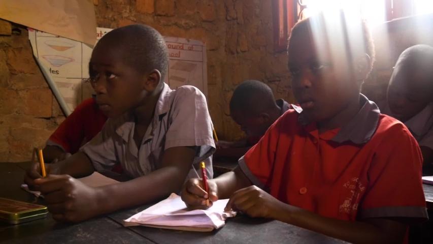 Namuwongo, Uganda - 11 07 2017: Panning shot of african schoolboys writting something in their books | Shutterstock HD Video #1030848314