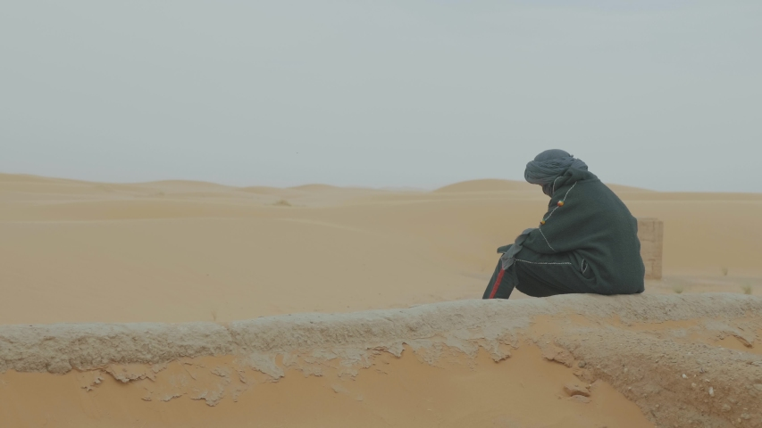 Man sitting on top of bright orange sand dunes in the Sahara desert in Morocco wearing a black head scarf in traditional clothing | Shutterstock HD Video #1030879874