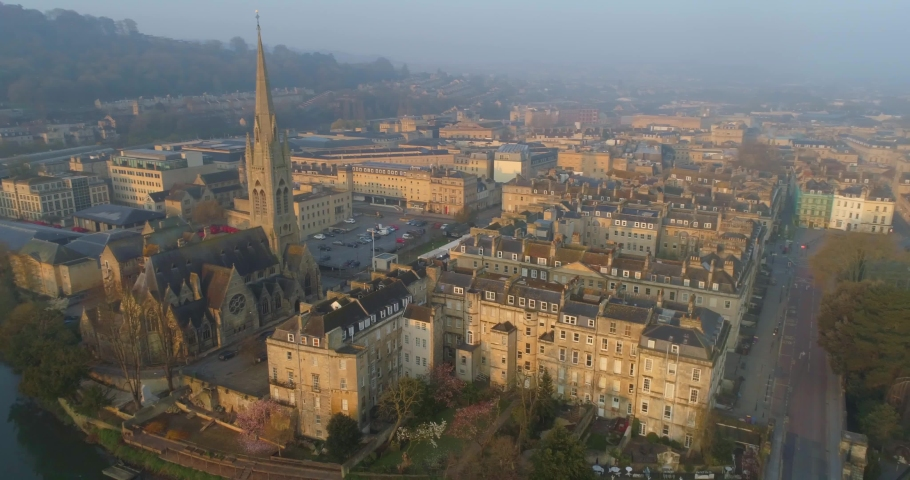 Aerial circling Bath's tallest spire of St John the Evangelist catholic church in the historic Roman city of Bath England amongst Georgian houses | Shutterstock HD Video #1030886024