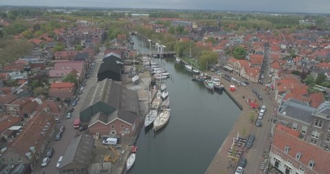 Aerial pulling back from sailing boats to reveal the Drommedaris Defence tower in historic Dutch town Enkhuizen in North Holland the Netherlands