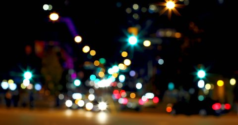 Front view of colorful bokeh of car lights at traffic signal on street at night. Car riding on the road