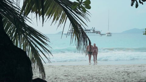 Seychelles. Praslin Island. Happy couple resting on the beach on island. Pretty woman in swimwear taking the hand of her husband. The man and woman on the sandy beach. Tourism, relax, vacation, travel