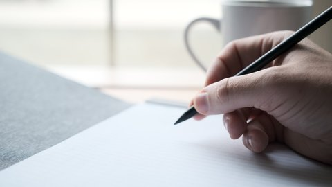 Writer's Block- Male Hand Hesitates while Holding Pencil on Blank Paper in front of Coffee Shop Window as Cars Go By