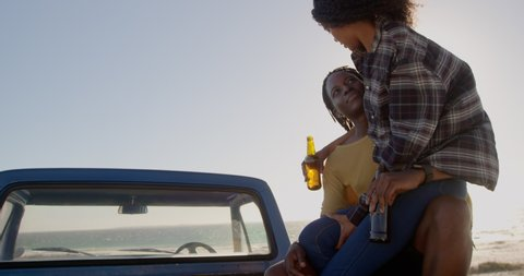African american woman on mans lap sitting on a pickup truck at beach. They are drinking beer