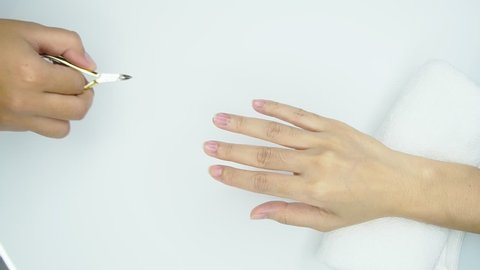 Beautician use clipper cleaning and cutting cuticle at nail and spa salon. Woman receiving fingernail manicure service by professional  manicurist at nail salon. Clean metal clipper by alcohol sheet.