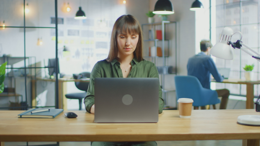 Young Beautiful Brunette Works on a Laptop Computer in Cool Creative Agency in a Loft Office. She has a Take-away Coffee and a Notebook on Her Table. Her Colleague Works in the Background. | Shutterstock HD Video #1030955354