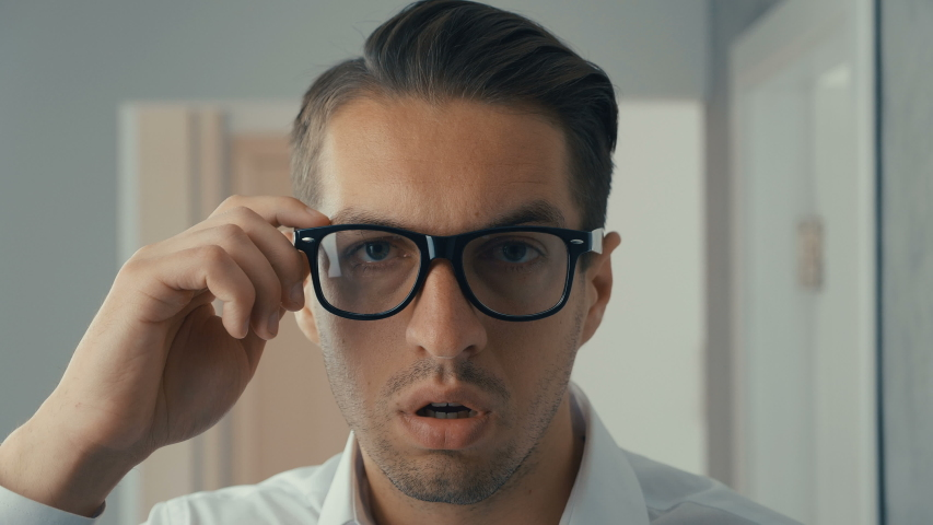 Young man is shocked and surprised. A man in surprise shoots glasses and looks at the camera in surprise. | Shutterstock HD Video #1030983164
