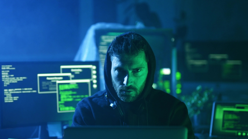 Portrait of sinister computer hacker working with codes breaking into security system in the company office at night. | Shutterstock HD Video #1030984154