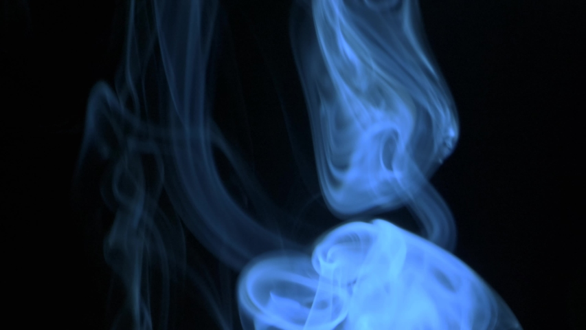 Thin trickle blue smoke slowly rising graceful twists up on black background. Cigar smoke blowing to top. Closeup, isolated on black background. | Shutterstock HD Video #1031052044