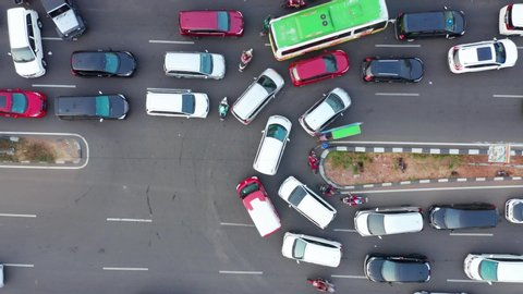 JAKARTA, Indonesia - May 27, 2019: Top down view of crowded cars moving slowly on street u-turn at rush hour. Shot in 4k resolution from a drone flying upwards