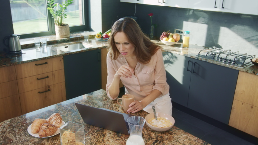 Businesswoman watching video in luxury kitchen. Topdown woman getting bad news during breakfast in luxury house. Upset woman closing laptop computer in modern kitchen.