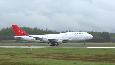 oslo airport norway - ca may 2019: Airplane jumbojet boeing 747 freight air cargo global landing panning right cloudy day