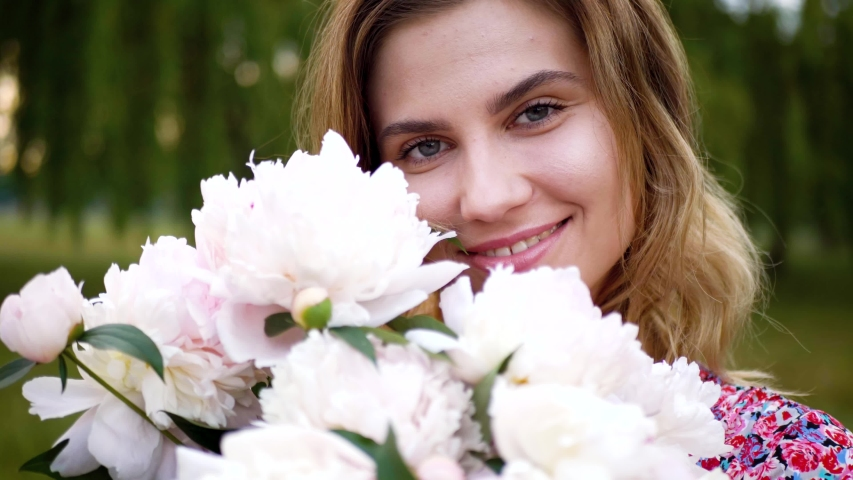 Beautiful Happy Young Woman Model Girl Posing with a Bouquet of Peonies #1031210594