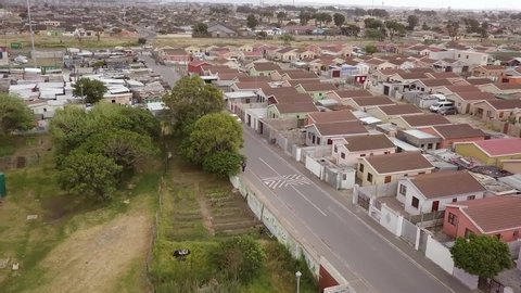 Aerial shot of low income, low-cost (rdp) housing across the road from a  tin shack informal settlement in a south african township