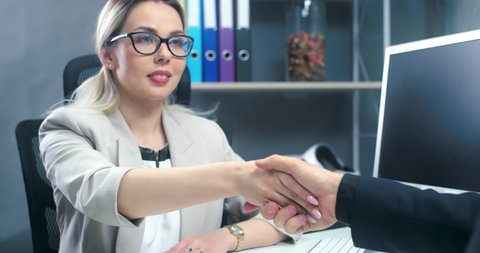 Hiring, woman in a suit, a businesswoman shaking hands with a man colleague, a handshake in the office.
