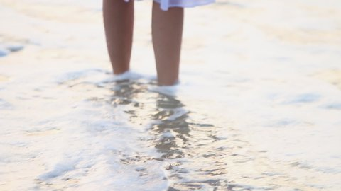 Sunset light on the water as gentle waves wash ashore around the legs of a woman in a white dress standing on the beach.