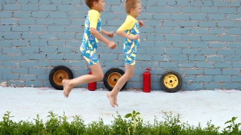 Funny kids in beautiful swimsuits for boys run and play in yard. boys are happy together and dream of adventure, travel, exploits