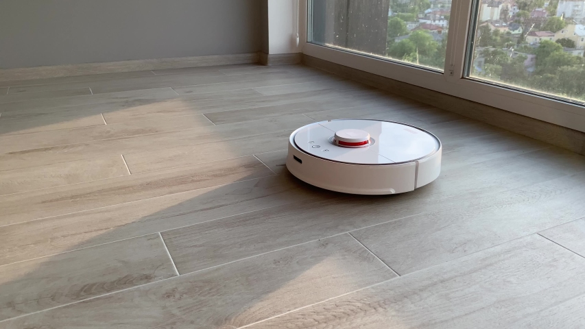 Smart home. Robot vacuum cleaner performs automatic cleaning of the apartment at a certain time