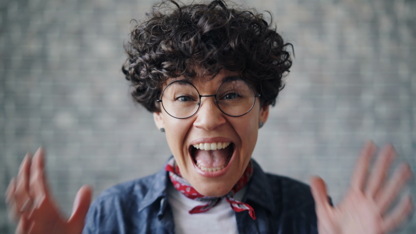 Close-up portrait of beautiful young woman screaming against gray brick background raising hands opening mouth closing eyes. Girl is wearing cool glasses. | Shutterstock HD Video #1031586974