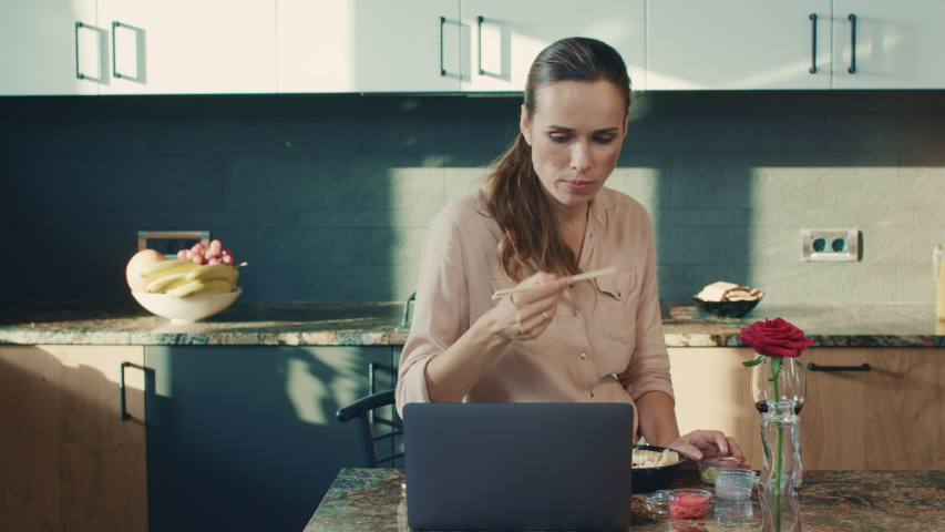 Beautiful woman eating sushi at luxury house. Upset woman watching laptop computer in modern kitchen. Sad female person reading news at computer in luxury house. | Shutterstock HD Video #1031592284