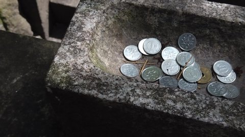 Japanese Shrine yen coins donation stone box. Top view. Coins were put on the stone  for praying. Slow motion.