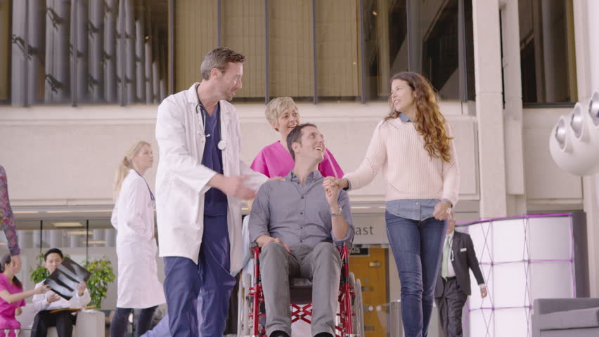 4K Caring medical staff assisting patient in a wheelchair in busy modern hospital   Shutterstock HD Video #10316924